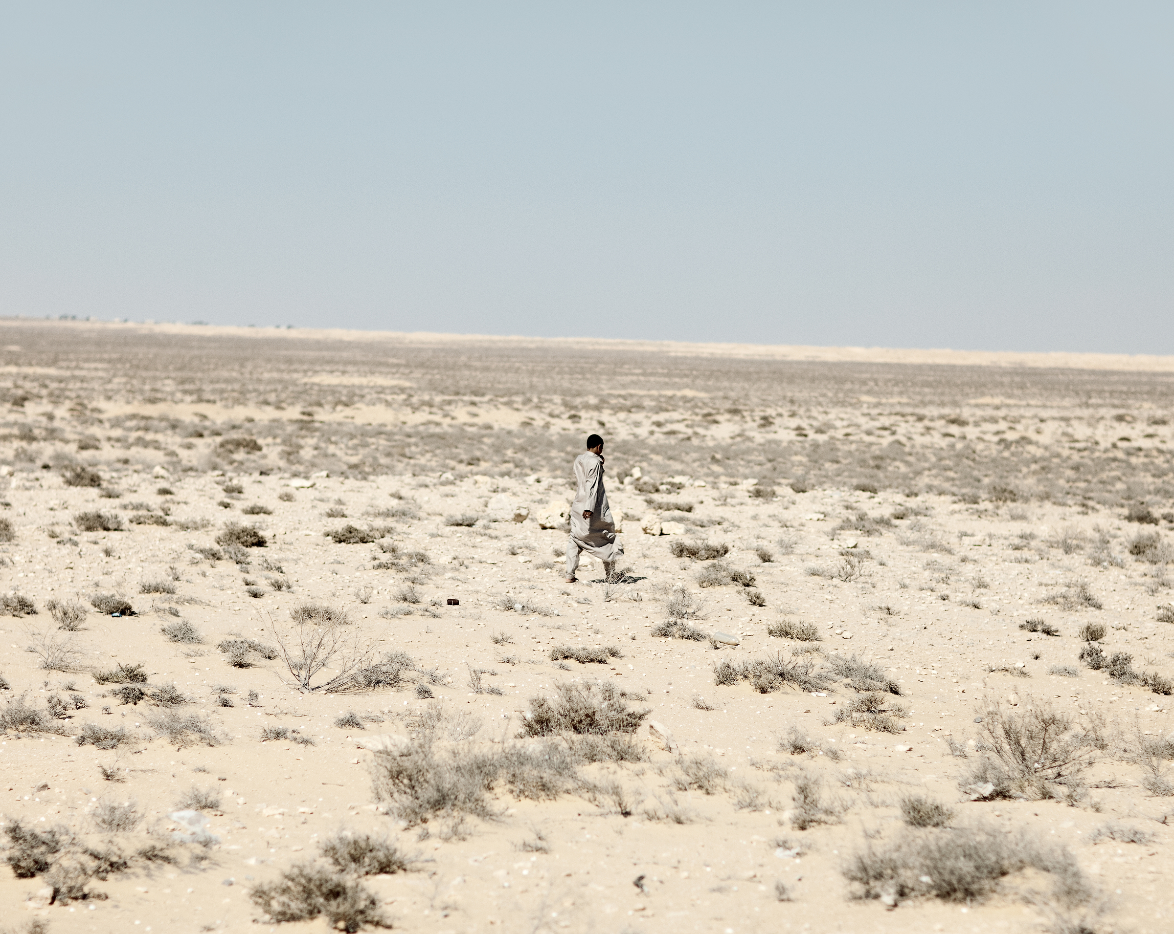 A boy walks in the desert south of El Alamein.