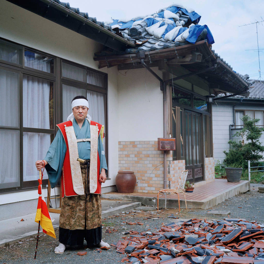 """Kunihito, 40 in front of his parents' house  """"I lived here since I was born until the disaster occurred. Roof tiles fell off and walls cracked due to the earthquake, but the house is habitable only if the level of radiation exposure was normal."""" Currently he lives in a leased housing in the town near Odaka with his family and has been working since before the disaster at the Fukushima Daiichi nuclear plant.  September 2012"""