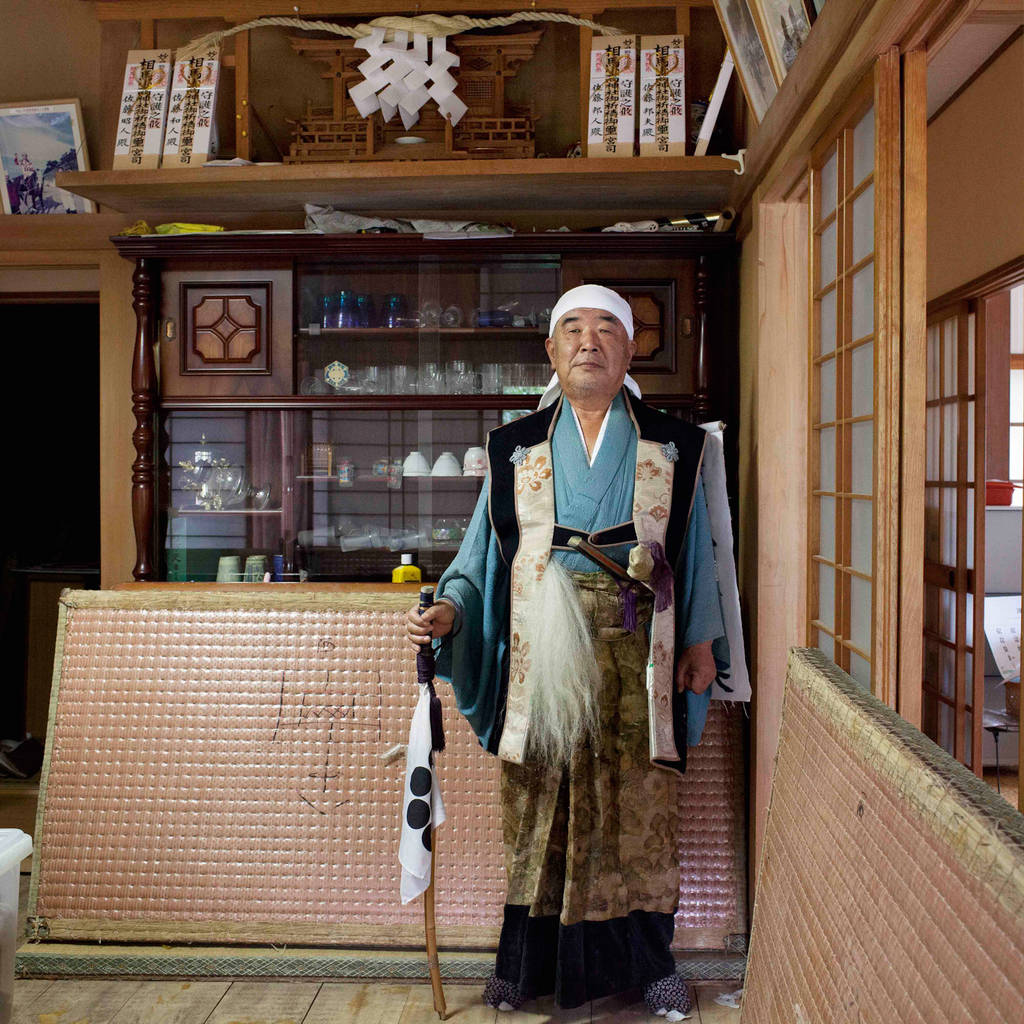"""Kunio, 65 in front of a household altar sacred to Odaka Shrine """"I used to stand in front of this kamidana (a household altar) sacred to Odaka Shrine and pray every morning when we were living here before the disaster."""" He prayed when somebody in his family got sick, when his daughter-in-law gave birth and also for other occasions. Standing solemnly in front of the kamidana with gratitude as part of his daily routine was such a precious and calm moment for him. He cannot live here anymore but he prays to the kamidana whenever he visits here.  August 2012"""